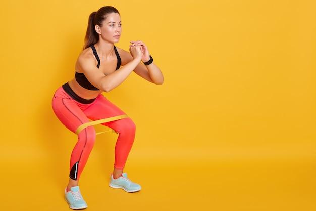 ジムでスクワットの運動の女性のクローズアップ、下半身の救済、スポーツ服を着てスポーティな女性と黄色のスタジオの壁に分離されたポーズのスニーカーを履いてスポーティな女性の抵抗バンドを行使フィットの女の子 Premium写真