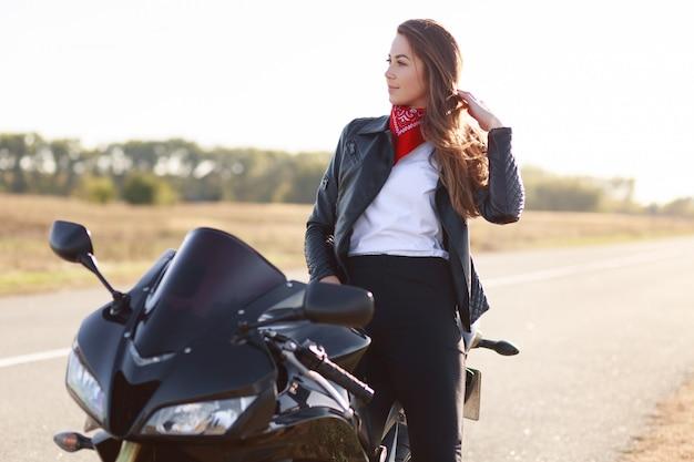 ライフスタイル、極端な人々の概念。ファッショナブルな服を着たかなり思慮深い若い女性ドライバーの横向きのショット、お気に入りのバイクの近くに立ち、屋外でポーズをとって、高速運転を楽しんでいます 無料写真