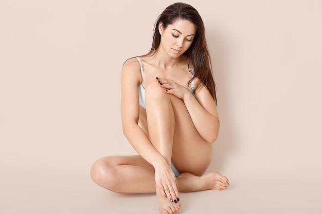完璧な体型のブルネットの女性、ブラでポーズ、完璧な滑らかな肌を示し、長い黒髪、ベージュの壁を越えたモデルが健康的なライフスタイルをリードしています。人、女性らしさと健康 無料写真