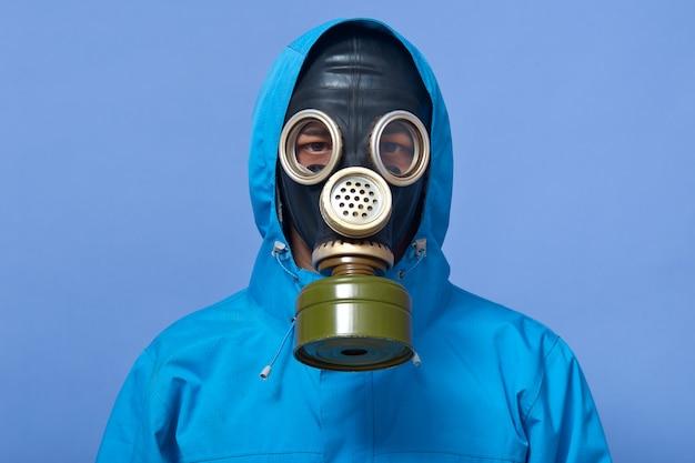 Образ эколога в противогазе пугает, заливая опасные химикаты на землю Premium Фотографии
