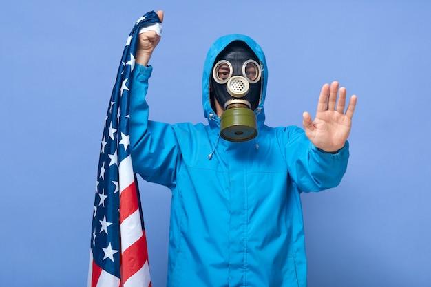 彼の手のひらで停止ジェスチャーを示す人工呼吸器を身に着けている科学者のスタジオ撮影 Premium写真