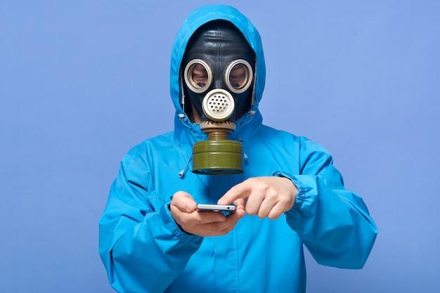 毒素エリアで働いている防毒マスクを着ている認識できない男のスタジオ撮影 Premium写真