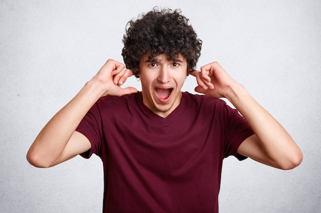 ストレスの多い巻き毛の男性がパニック状態で耳を塞ぎ、大きな刺激的な音を避けます 無料写真