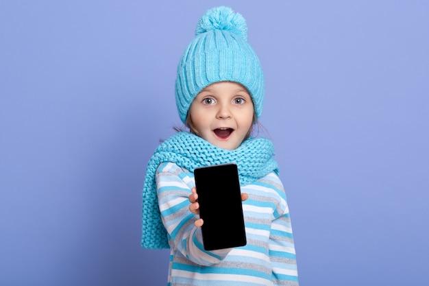 空白の画面を表示するポンポンと冬の帽子をかぶってびっくりした小さな女の子子供 Premium写真
