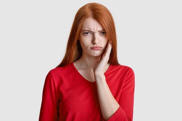 そばかすのある皮膚の不機嫌な赤い髪の女性は、頬に手を保ち、歯痛に苦しみ、感度があり、白で隔離され、カジュアルな赤い服を着ています。歯科問題の概念 Premium写真