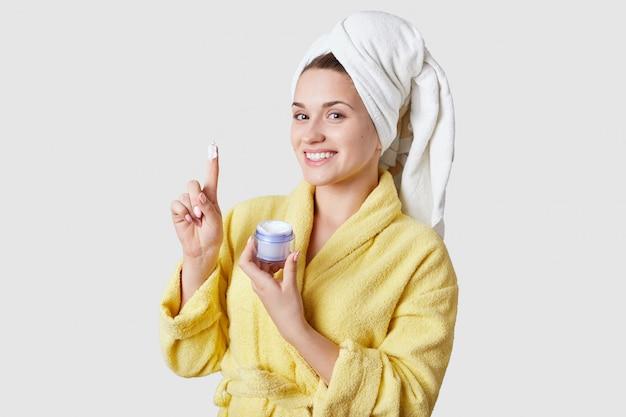 人、フェイシャルトリートメント、美容のコンセプトです。こぼれるような笑顔で健康的な美しい若い女性は、肌にクリームを使用し、シャワー後、白いスタジオのモデルの家庭服を着ています。 Premium写真