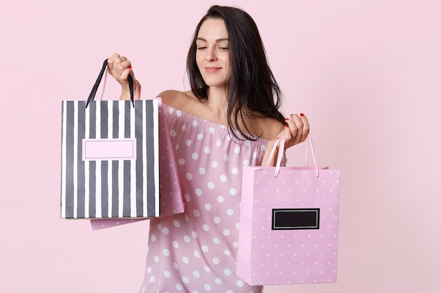 Удивительная молодая брюнетка в платье в горошек, позирует с сумками и смотрит вниз с задумчивым выражением лица, стоя на розовом, имеет подарок на день рождения. Бесплатные Фотографии