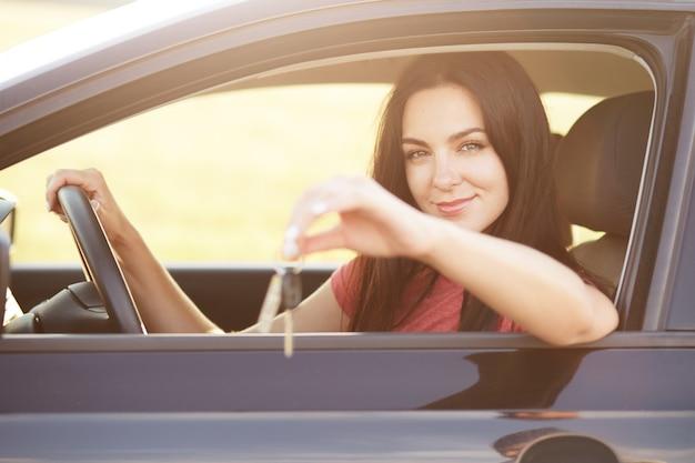 女性は運転席に座り、ハンドルを握り、広告を出したり、車を売ったりします。美しいブルネットの女性は車を運転します 無料写真