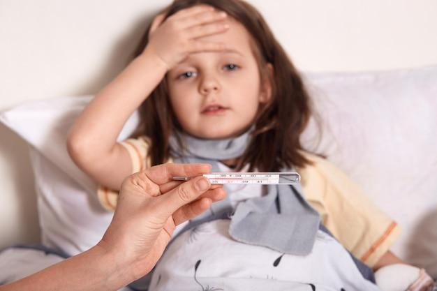 Мать держит в руках термометр, больная маленькая девочка лежит в постели и держит ладонь на предхие, страдает от высокой температуры Бесплатные Фотографии