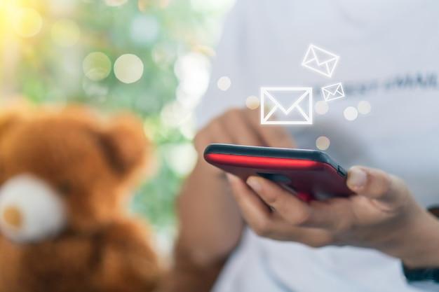 スマートフォンを使用してメールを送受信する女性の手。 Premium写真