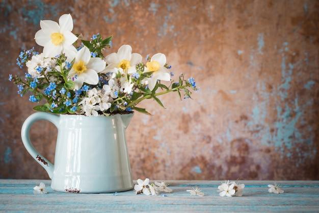 古い木製の塗られたテーブルの水差しの春の花 Premium写真