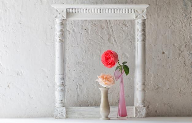 Розы в вазе на старом белом Premium Фотографии