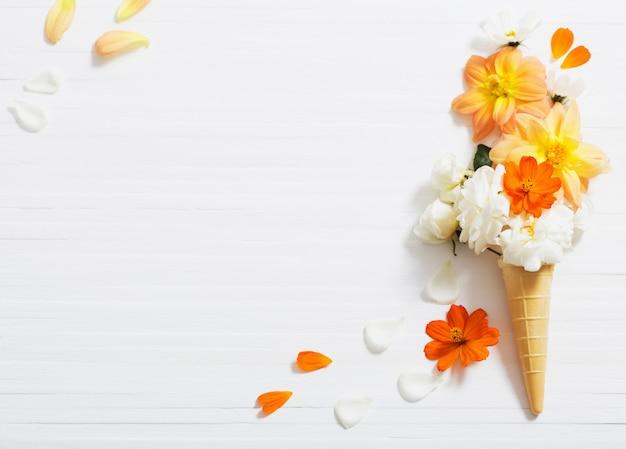 白い木製の背景にワッフルコーンの花 Premium写真