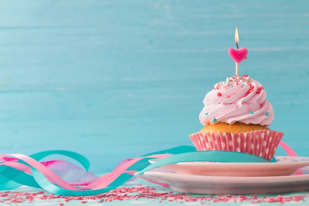 青い木製のテーブルにピンクのカップケーキ Premium写真