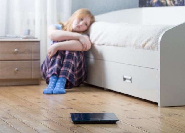床のスケールを持つ悲しいティーンエイジャーの女の子 Premium写真