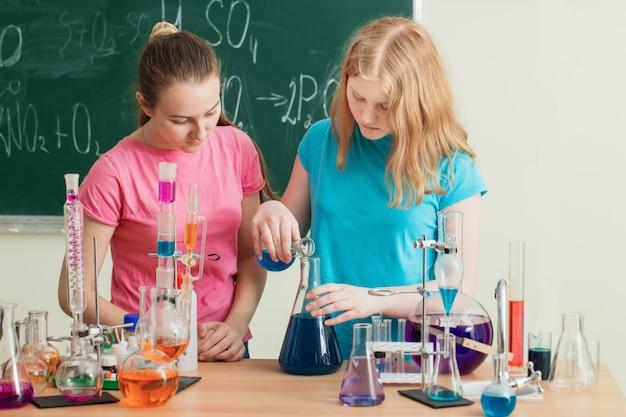 Две девушки делают химические эксперименты Premium Фотографии