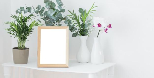 Деревянная рама на винтажной белой полке с цветами и растениями Premium Фотографии