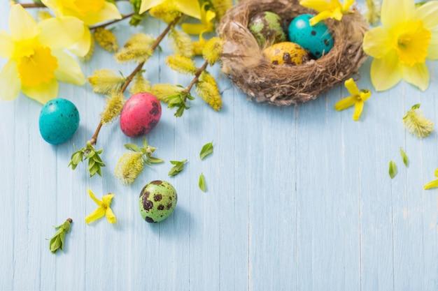 木製の背景の春の花と巣のイースターエッグ Premium写真