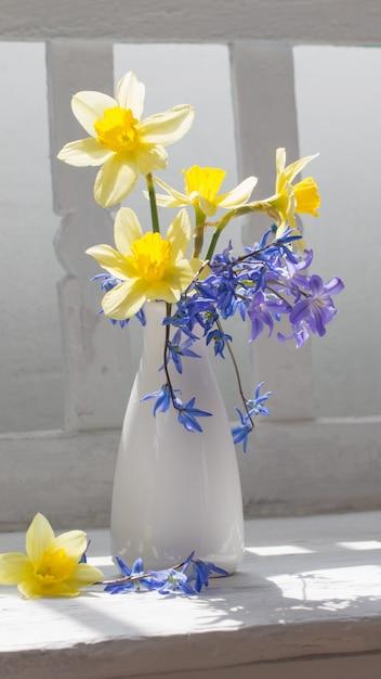 Весенние цветы в вазе на белой деревянной скамейке Premium Фотографии