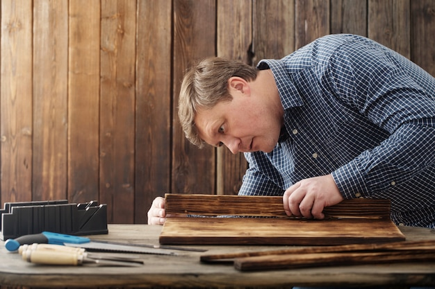 大工が木製の壁にツールを操作 Premium写真