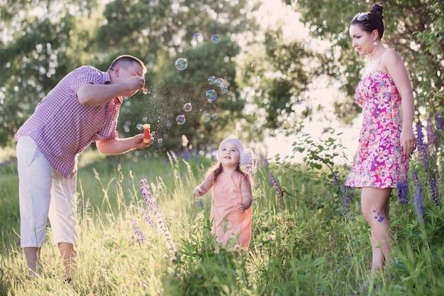 幸せな母、父と娘が公園でシャボン玉を吹く Premium写真