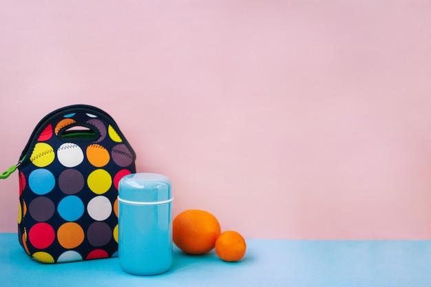 Перекус на ланч-боксе. красочная сумочка, синий термос, апельсин, мандарин. розовый. Premium Фотографии