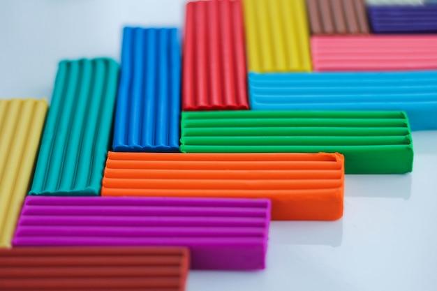 Разноцветный пластилин - это материал для творчества с детьми. моделирование и развитие мелкой моторики. школьные принадлежности на голубом Premium Фотографии