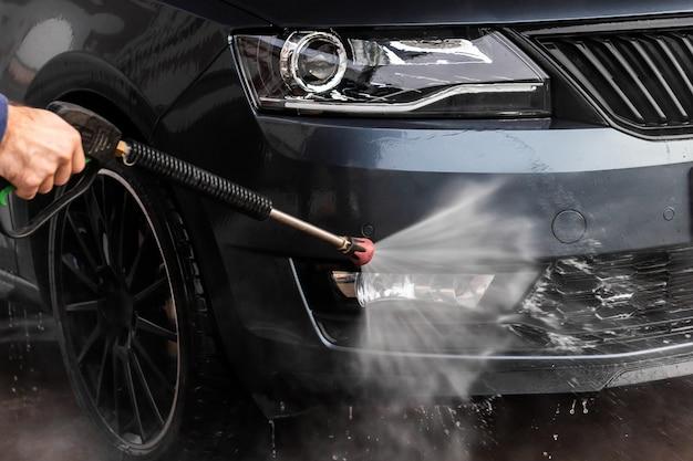 男はセルフサービスの洗車で車を洗っています。水できれいな高圧車両洗浄機。洗車設備、ムラダボレスラフ、 Premium写真