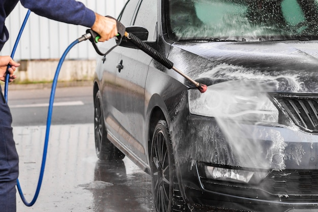 男はセルフサービスの洗車で車を洗っています。高圧車両洗浄機は泡をスプレーします Premium写真