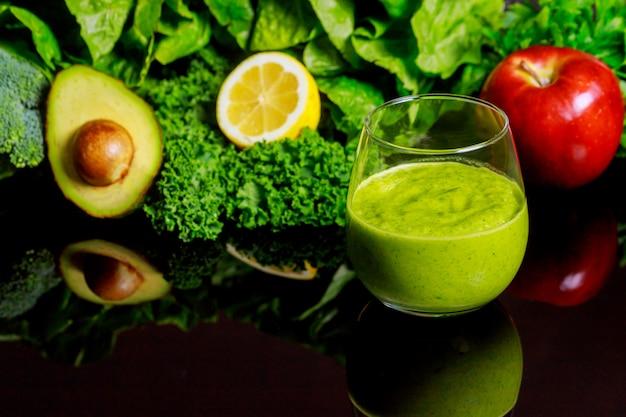 黒い背景に食材を使った新鮮な野菜のスムージー。 Premium写真