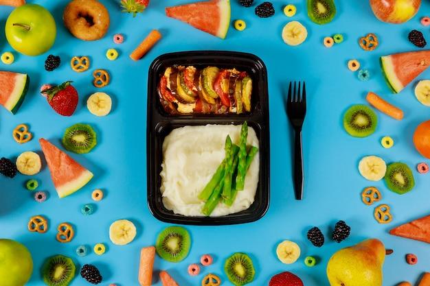 Контейнер с обедом на фоне свежих фруктов и овощей. Premium Фотографии