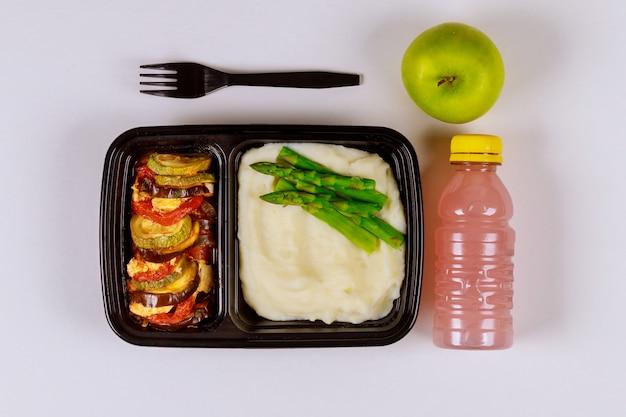 ドリンクとリンゴと食品容器で食べる準備ができた食事。 Premium写真