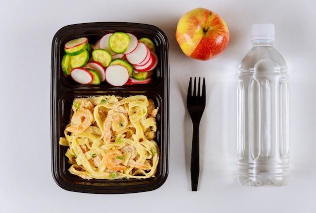 水とリンゴと一緒に食品容器で食べる準備ができた食事。 Premium写真