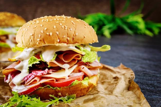 Медовый сэндвич с ветчиной, листьями салата, помидорами и сыром Premium Фотографии