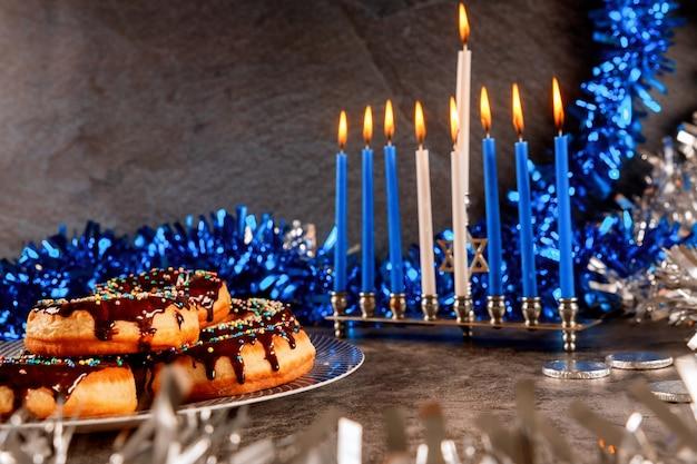 ハヌカ本枝の燭台、ドーナツ、チョコレートコイン、装飾 Premium写真