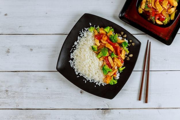 Рис с жареной курицей и овощами на черной квадратной пластине. китайская кухня. Premium Фотографии