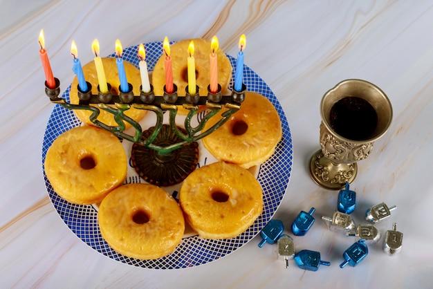 非常に熱い蝋燭、ドーナツ、銀の杯のワインと本枝の燭台 Premium写真