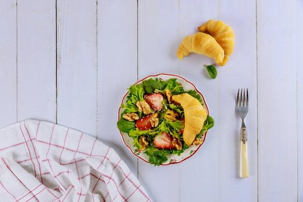 Весенний зеленый салат с клубникой, грецкими орехами и круассаном. Premium Фотографии