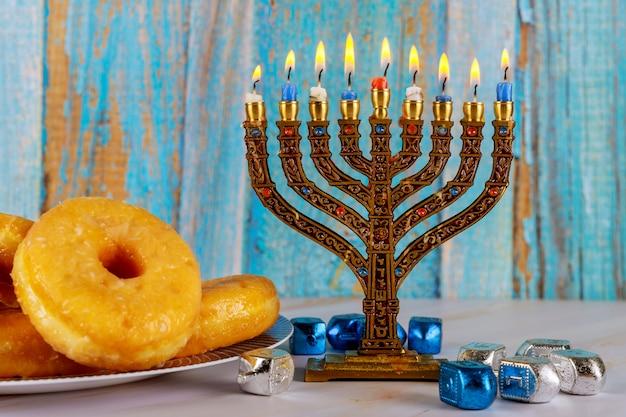 本枝の燭台、ドーナツ、ドレイドルとユダヤ人の祝日のハヌカ Premium写真