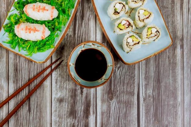 アメリカンフットボールゲームパーティーのおいしい寿司と醤油と箸のロール Premium写真