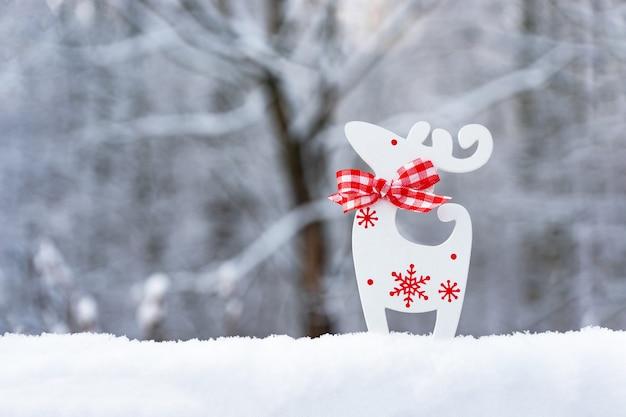 雪、雪、白い背景をぼかした写真に白い鹿のクリスマスカード。明けましておめでとうございます。冬の背景。コピースペース。 Premium写真