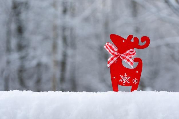雪、雪片、自然な背景をぼかした写真にレッドディア付きのクリスマスカード。明けましておめでとうございます。冬の背景。コピースペース。 Premium写真