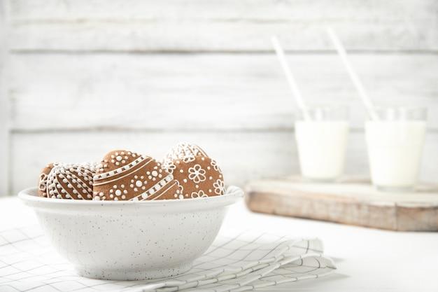 イースタークッキーと牛乳のガラスのプレート。イースター。イースタークッキー。テキストのための場所。 Premium写真