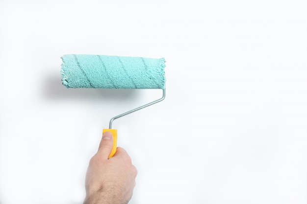 Парень красит стену в синий цвет строительным валиком Premium Фотографии