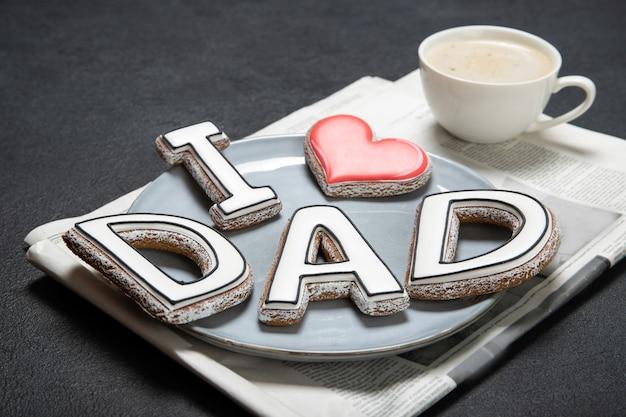 Счастливый день отца концепции. вкусное печенье и чашка кофе на деревянном фоне Premium Фотографии