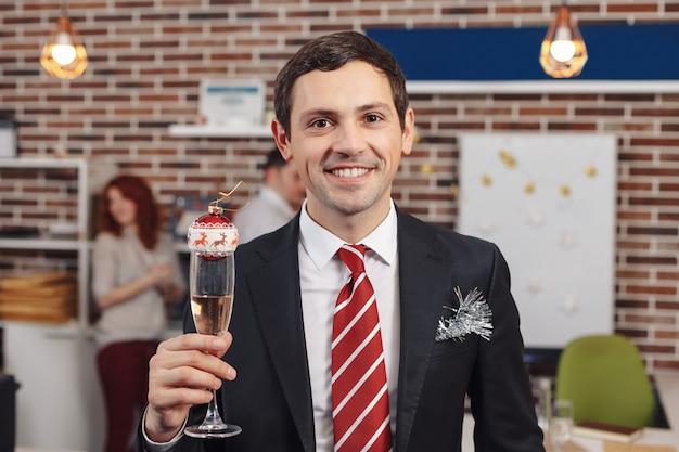 Улыбающийся бизнесмен, держа бокал с шампанским Premium Фотографии