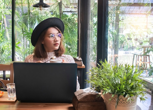 コーヒーショップカフェでアジアの女性 Premium写真
