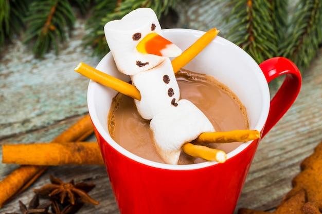 Красная кружка с горячим шоколадом с растопленным зефиром снеговика Premium Фотографии