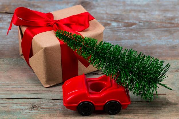 おもちゃの車とギフトに緑のクリスマスツリー。クリスマスの休日のお祝いのコンセプト Premium写真