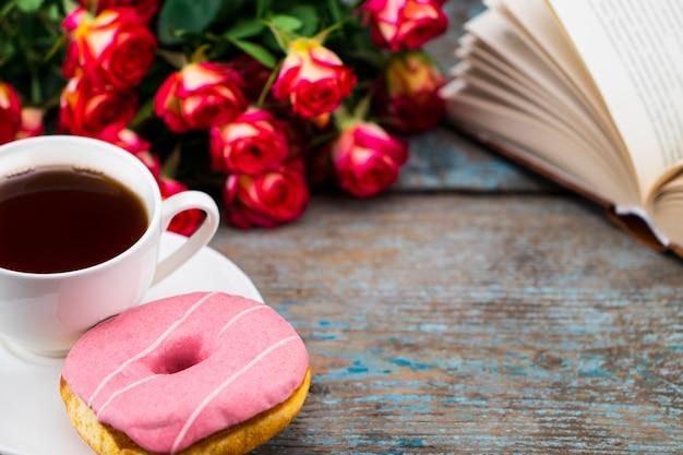 ドーナツ、新鮮なバラ、木製の本とお茶のカップ。 Premium写真